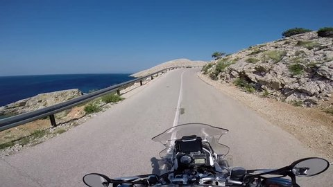 HERTVISI. GEORGIA. MAY 2016: The motorcycle traveler on the bare mountain plateau near the blue sea and the winding road amid rolling hills under Sunny skies . the first person. HERTVISI. GEORGIA