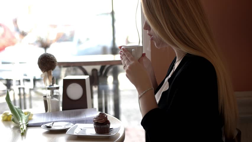 Young Business Woman Sitting at a Table in a Cafe and Drink Coffee | Shutterstock HD Video #25359950