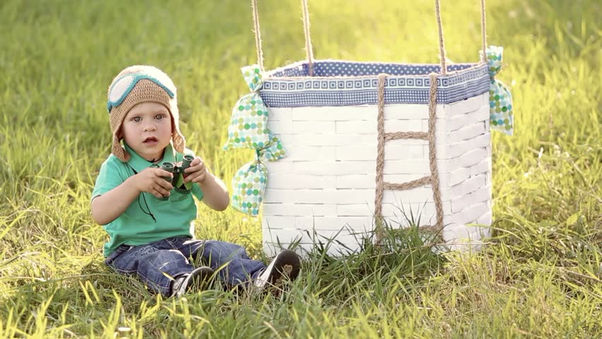 Beautiful funny little child wearing knitted pilot hat sits near handmade toy airballoon in green grass. Portrait of cute baby looking at camera smiling happily. Real time full hd video clip.