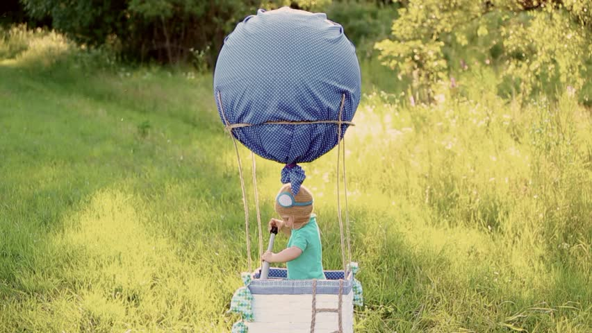 Beautiful funny little child wearing knitted pilot hat plays in handmade toy airballoon in nature landscape. Portrait of happy cute excited baby. Real time full hd video footage.