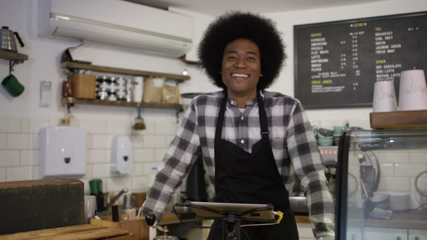 4K Portrait of friendly smiling worker standing behind counter in coffee shop #25361261