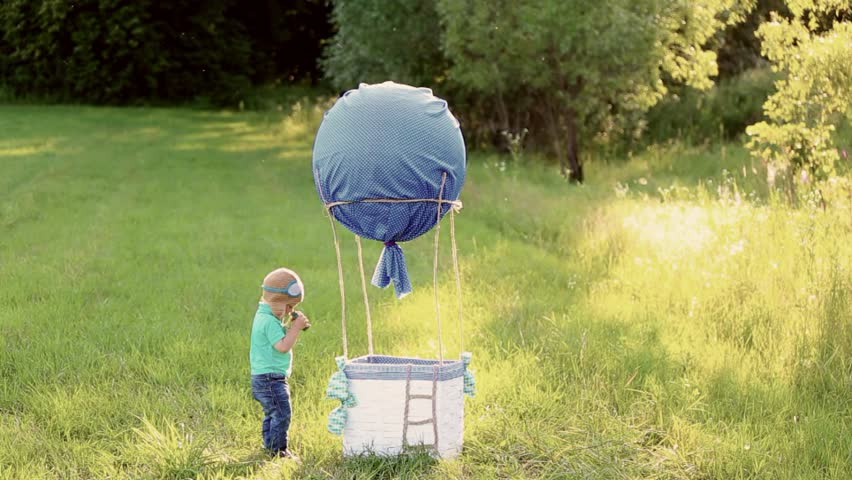 Beautiful funny little child wearing knitted pilot hat plays near handmade toy airballoon in nature landscape. Baby looks through binoculars. real time full hd video footage.