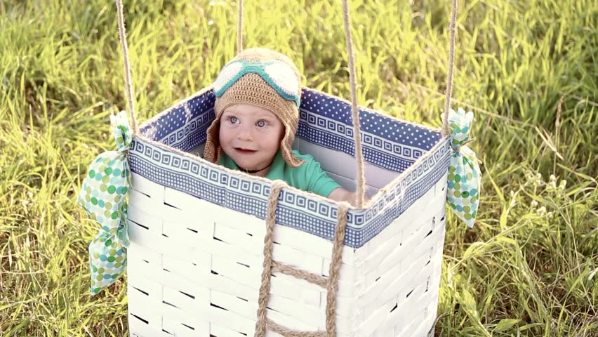 Beautiful funny little child wearing knitted pilot hat sits in handmade toy airballoon in green grass. Portrait of cute baby looking at camera smiling happily. Real time full hd video clip.