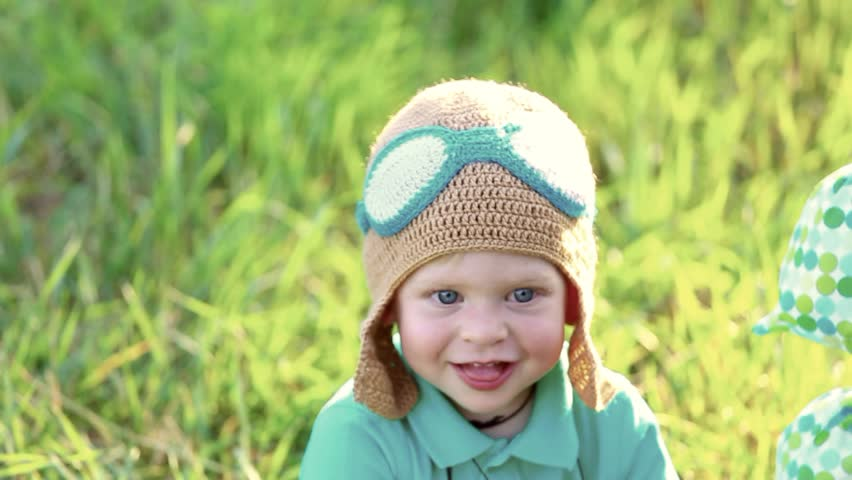 Beautiful funny little child wearing knitted pilot hat sits near handmade toy airballoon in green grass. Closeup portrait of cute 1 year old baby looking at camera smiling happily.