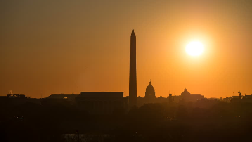(Time-lapse) The sun rises over the skyline including the Lincoln Memorial, Washington Monument and US Capitol building near the spring equinox in Washington, DC. See separate clip without lens flare.