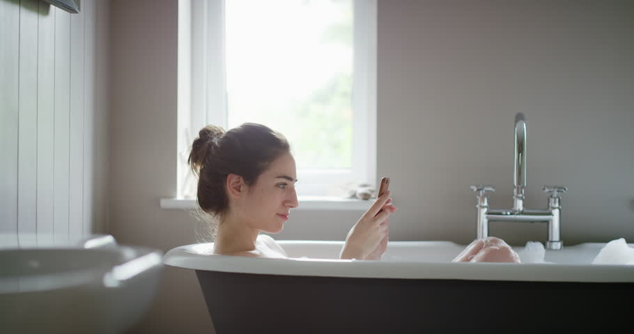 Beautiful Woman relaxing in bubble bath lying in bathtub using smartphone browsing social media sharing photos mindfulness health concept