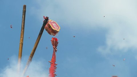 Red firecracker explodes against blue sky. Full HD 1080p video footage