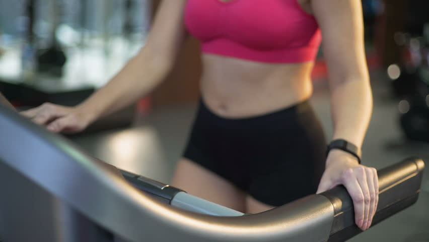 Sportive slim woman walking and running on treadmill, active exercising in gym | Shutterstock HD Video #25394795