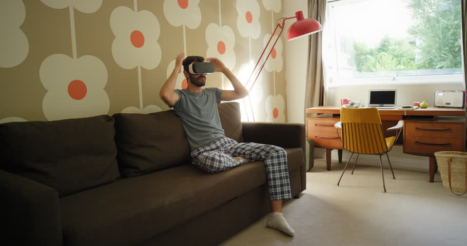 Young Man wearing virtual reality headset sitting on sofa at home watching 360 video imagination concept in retro styled modern apartment #25399010