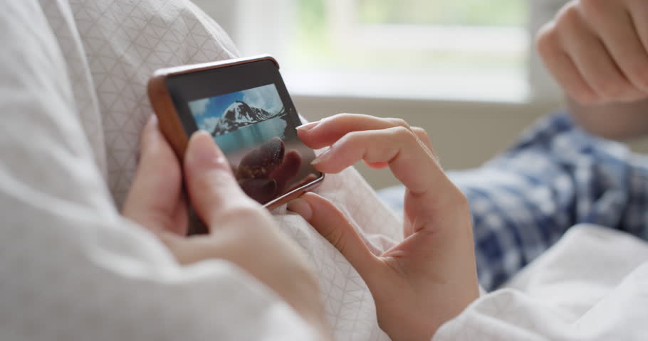 Closeup Woman using smartphone in bed scrolling travel photos on touch screen browsing social media sharing wanderlust at home   Shutterstock HD Video #25401536