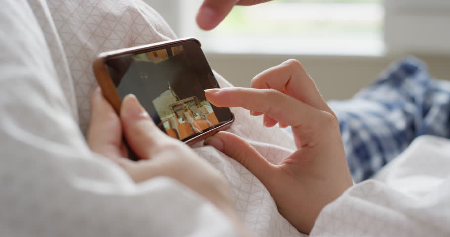 Closeup Woman using smartphone in bed scrolling travel photos on touch screen browsing social media sharing wanderlust at home   Shutterstock HD Video #25401632