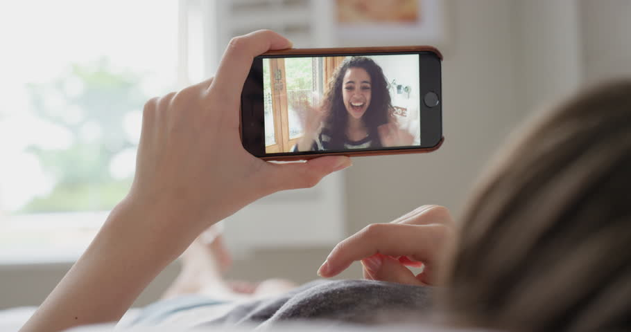 Young woman having video chat holding smartphone webcam chatting to girlfriend lying in bed at home | Shutterstock HD Video #25402955