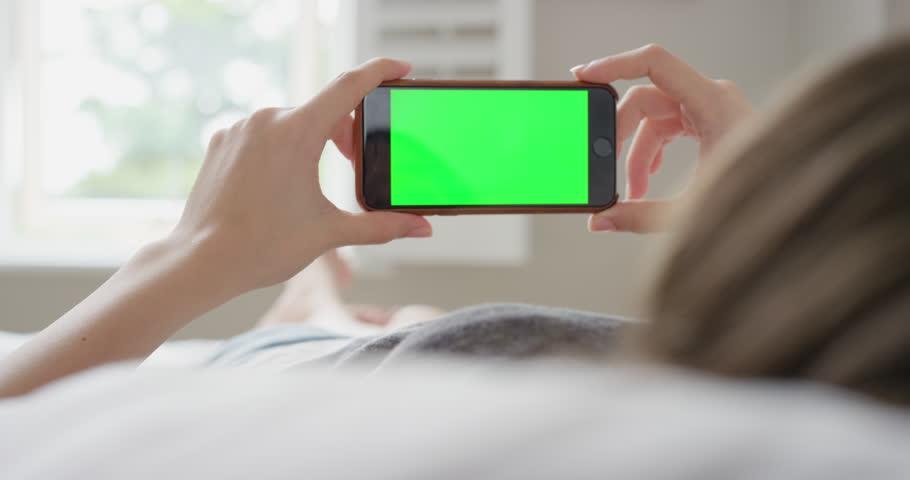 Close up Woman holding smartphone green screen chroma-key greenscreen sharing authentic social media