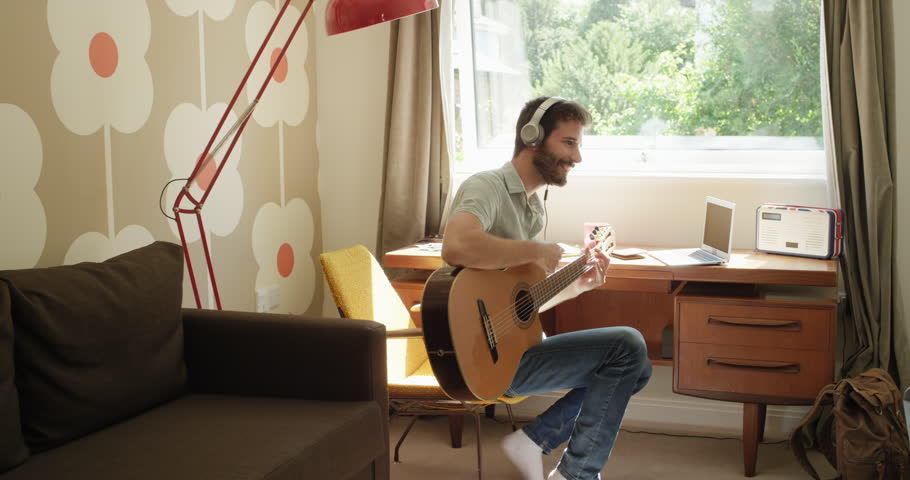 Attractive hispanic man sitting at window learning to play guitar using laptop computer at home in retro styled trendy apartment | Shutterstock HD Video #25406648