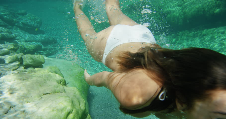 Woman swimming underwater in slow motion wearing white bikini diving down in clear blue tropical water