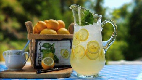 Man placing 2 glasses of lemonade by Pitcher of lemonade on table outside