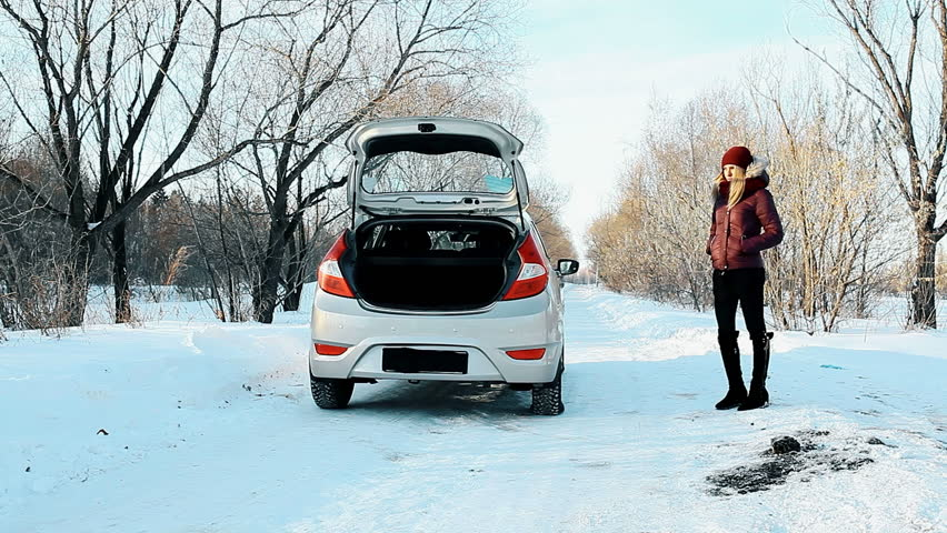 The girl broke the car in the winter forest