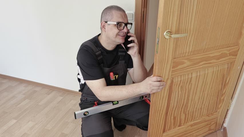 Man with spirit level near doors talking on phone #25418612
