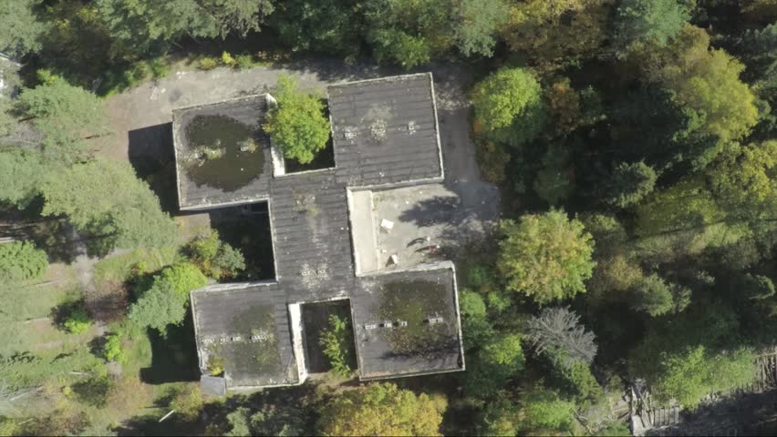 Flying over the the building in the middle of the forest. Aerial survey of the exterior of abandoned hospital.