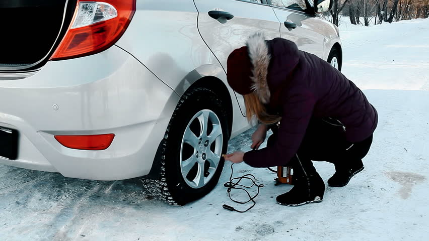 A girl is pumping up a flat tyre in winter