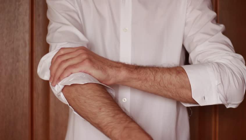Man unbuttoning his shirt's sleeves