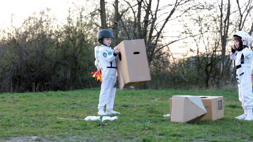 Two adorable children, boy brothers, playing in park on sunset, dressed like astronauts, imagining they are flying on the moon #25458536