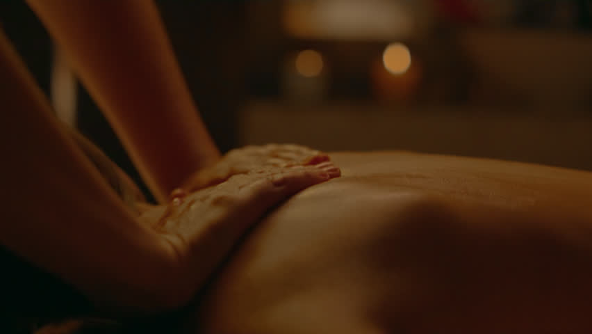 Receiving Body Massage at Spa Club.  Hands massaging the back. Camera on dolly. Evening light.