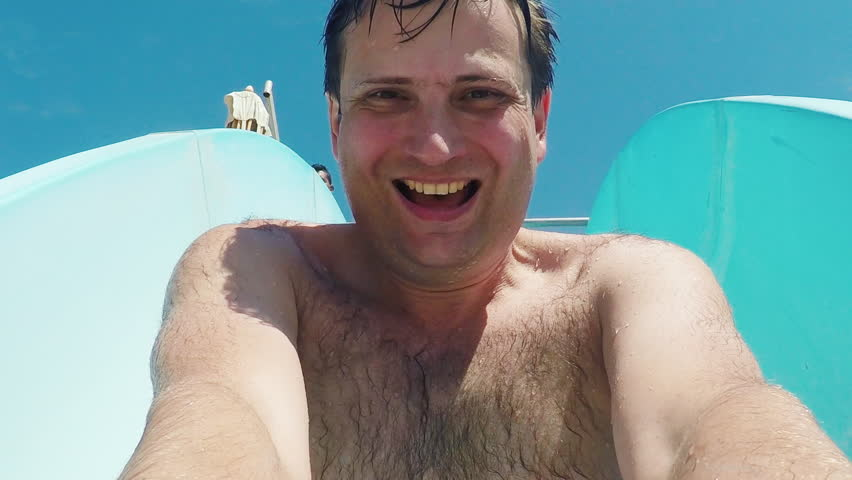Portrait of a young cool man, descends into the water slide in the water park, shoots himself on video. Slow Motion Picture