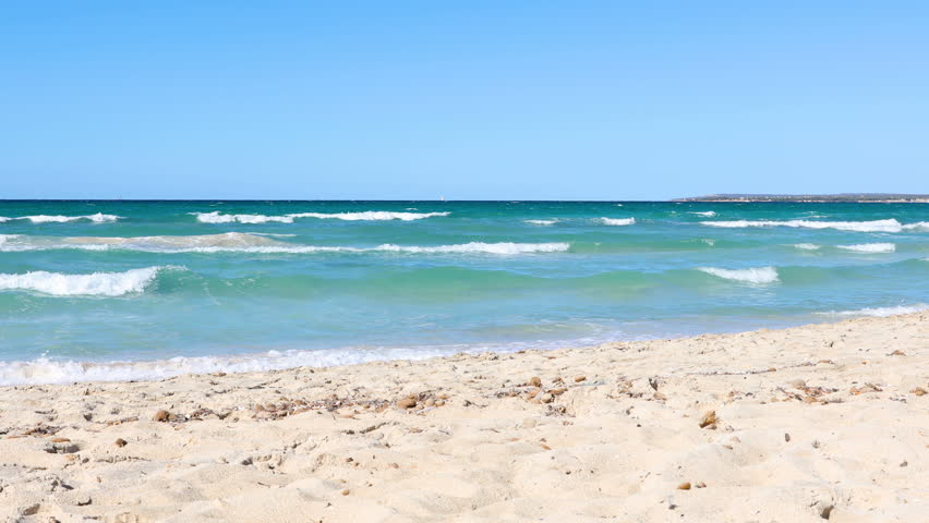 Waves and beach at seaside in Majorca, summer season background and concept with sea, blue sky and relaxing mood. Travel and holidays themes