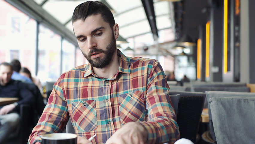 Handsome man in colorful shirt connects headphones to smartphone and plays music  | Shutterstock HD Video #25486466