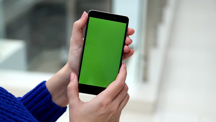 Closeup of young female caucasian hand holding modern smartphone with green blank screen as if filming or watching something  in big mall. Real time full hd video footage | Shutterstock HD Video #25491035