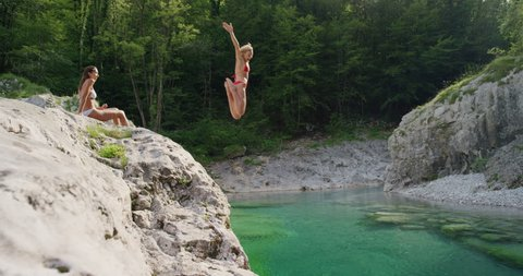 Young woman jumping into clear blue water swimming in river on bright sunny Brave athletic girl swimmer enjoying summer day in nature outdoors