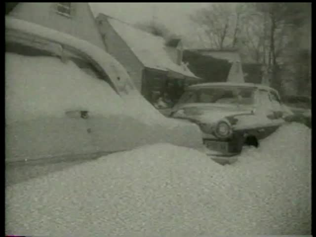 Cars are buried in snow on streets in towns during and after a snowfall in the USA circa 1958 - MGM PICTURES, UNIVERSAL-INTERNATIONAL NEWSREEL, USA, filmed in 1958
