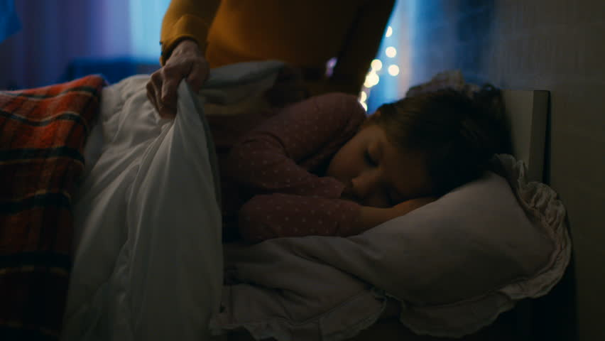 Sweet Little Girl Sleeps in Her Bed at Night, Her Mother Tucks Her Blanket in. Shot on RED EPIC-W 8K Helium Cinema Camera. #25513337