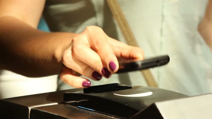 Closeup  female hand with manicure bring the phone to  ntfs system reader in metro turnstile for payment of fare | Shutterstock HD Video #25526678