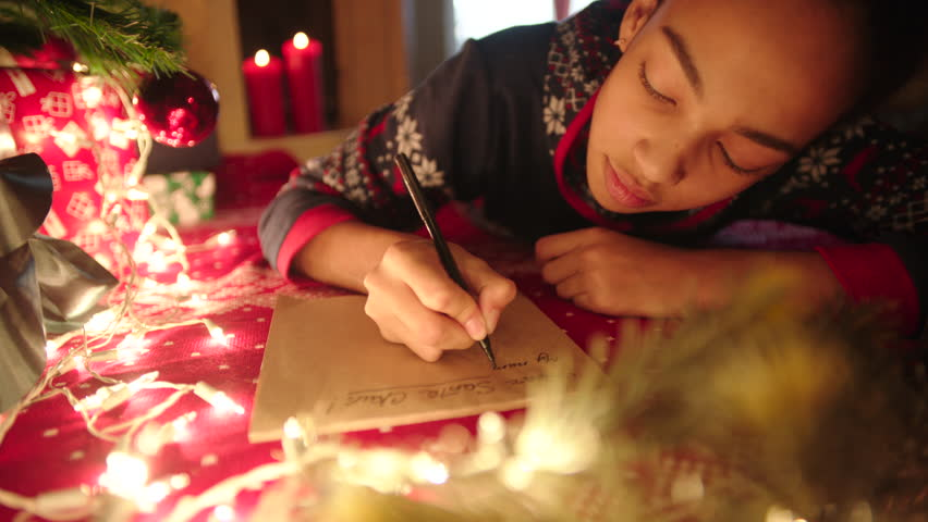 Teen girl is lying near decorated christmas tree and writing christmas letter to Santa Claus | Shutterstock HD Video #25558070