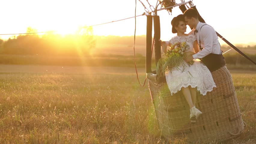 The portrait of the happy vintage dressed couple sitting on the moving airballoon in the field during the sunset. The beautiful woman is petting the face of the lovely man and holding the bouquet.