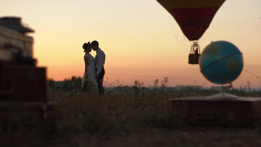 The lovely vintage dressed couple is kissing near the globe, vintage suitcases and flying aerostat. The field location during the sunset.