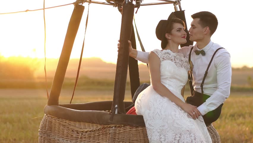 The close-up portrait of the pretty vintage dressed couple holding hands and sitting on the air-balloon placed in the field during the sunset.