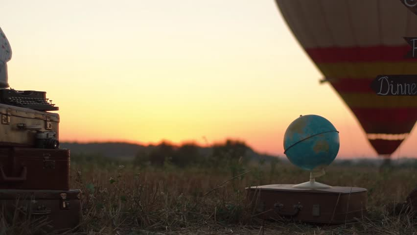 The composition of the globe placed on the brown suitcase next to the vintage suitcases at the background of the aerostat in the field during the sunset.