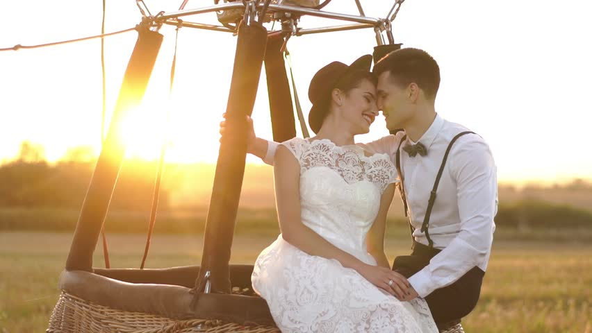The vintage dressed couple are holding hands and laughing while sitting on the moving air-balloon located in the sunny field during the sunset.