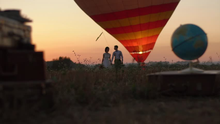 The blurred globe and vintage suitcases are placed in the front of the happy walking couple near the aerostat in the field during the sunset.