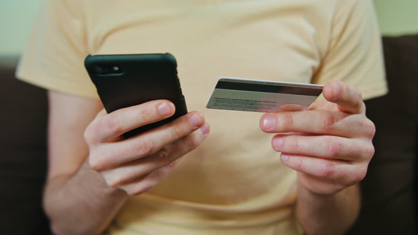 Man weared in t-shirt shopping with a credit card in one hand and a smartphone on the other. #25567907