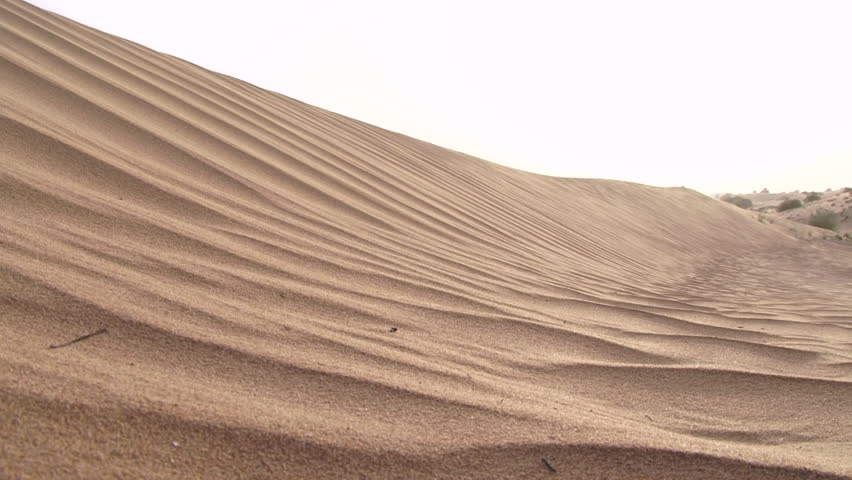 Desert time lapse. Medium long-shot of the ripples on a dune as the wind blows sand across the desert. #25579496