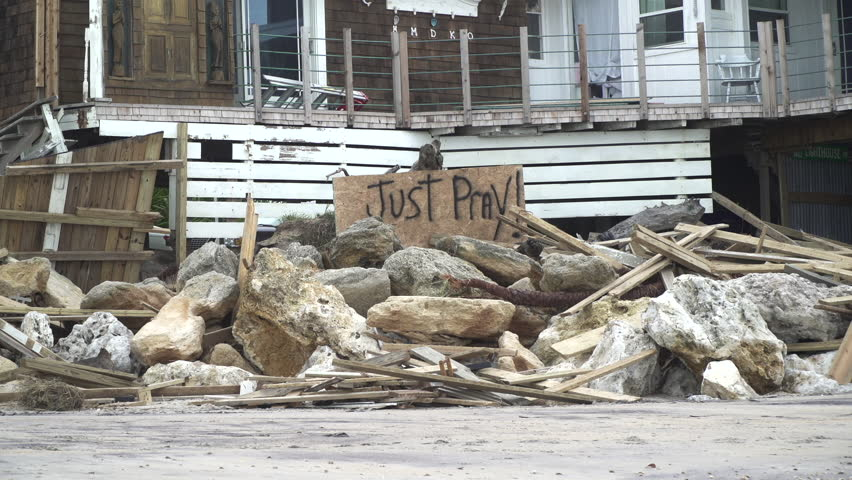 "A sign saying ""just pray"" put outside a damaged home after a hurricane hit."