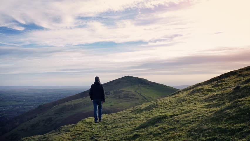 Man Walks Over Hilltop At Sunset | Shutterstock HD Video #25603019