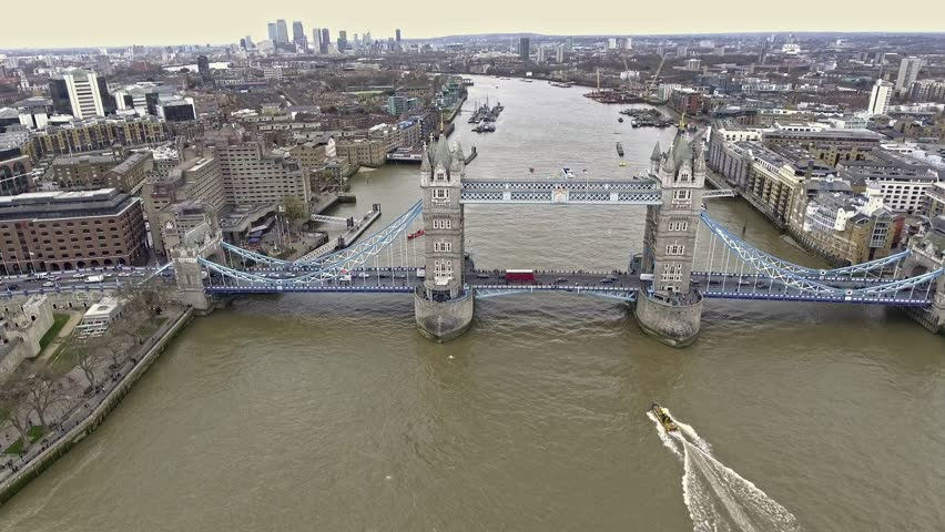 Aerial Shot of Flying Over Tower Bridge and River Thames in London, UK feat. Skyscrapers and Business Office Buildings in the Background with Boats and Car Transportation Vehicles in 4K Ultra HD   Shutterstock HD Video #25604672
