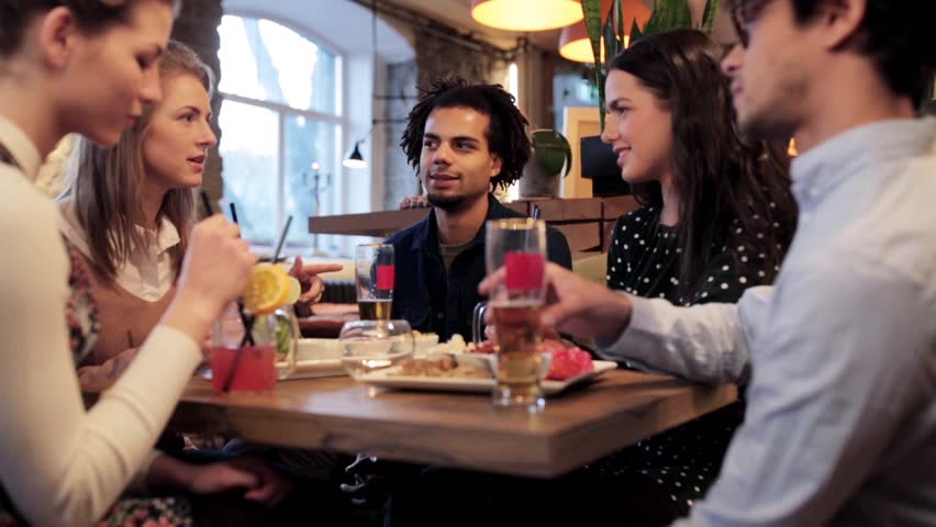 leisure, food, drinks, people and holidays concept - happy friends eating and drinking at bar or cafe #25606145