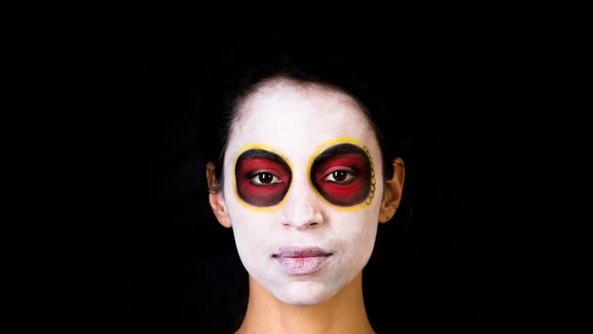 Beautiful woman with custom designed candy skull mexican day of the dead face make up. this is a stop motion of the make up being applied to the face.