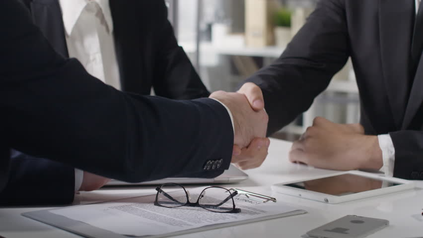 Closeup of three coworkers sitting at business meeting in office. Men shaking hands while discussing partners agreement #25631360